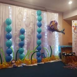 BESPOKE UNIQUELY DESIGNED UNDER THE SEA BACKDROP WITH BALLOON DECOR, LED WHITE CURTAIN AND UNDER THE SEA INSPIRED AND THEMED PROPS