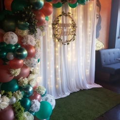 RUSTIC INSPIRED PHOTO BACKDROP WITH ORGANIC BALLOON ARCH WITH FLOWERS AND LEAVES